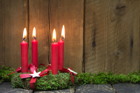 Advent or christmas wreath with four red wax candles on wooden background  photo