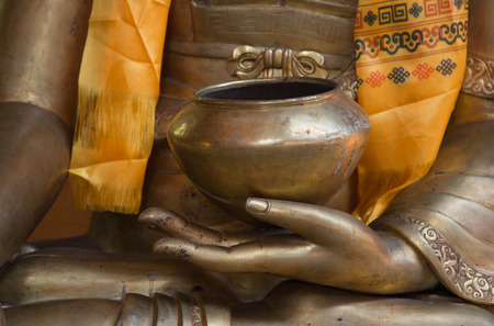 Buddha hands holding golden bowl. photo