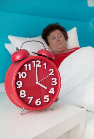 sleeplessness: Senior donna a letto malato e sofferto di insonnia. Archivio Fotografico