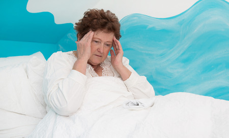 suffered: Portrait of a senior woman lying ill with headache in the bed.