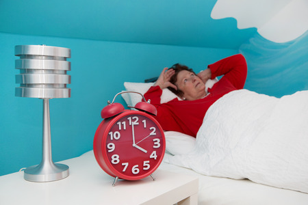 insomnia: Senior woman in bed ill and suffered of sleeplessness.