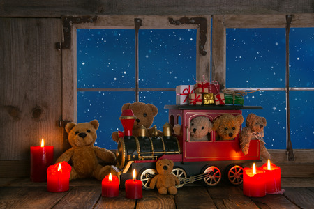 Teddy bears and red candles decorated on an old windowsill background with view out in the nigth.