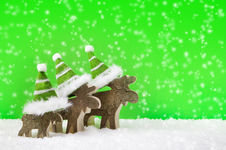Three wooden reindeer for christmas on a green background with snow for a greeting card. photo