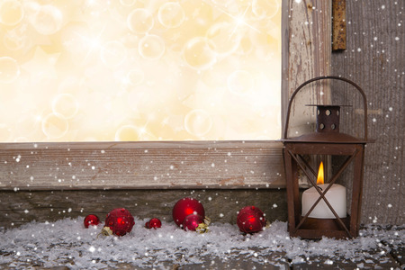 windowsill: Christmas wooden background with an old rustic latern and red balls.