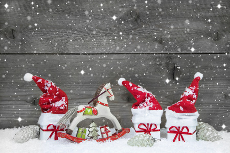 horse in snow: Wooden christmas background in Grey with red hats, presents and a rocking horse. Stock Photo