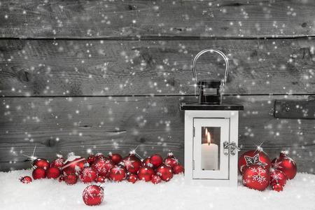 atmosfera: Blanco shabby latern elegante para la Navidad con velas y bolas rojas sobre un fondo de madera gris.