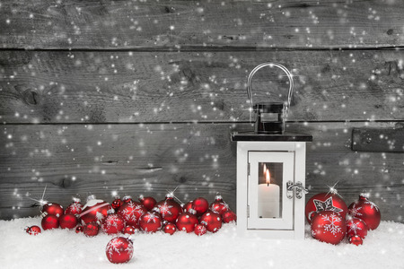 White shabby chic latern for christmas with candle and red balls on a grey wooden background. Stok Fotoğraf - 28446857