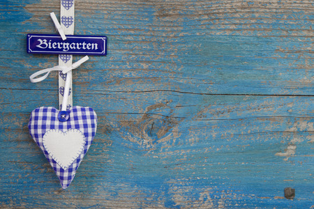 octoberfest: Bavarian blue white checked heart on wooden with sign beergarden in german letters