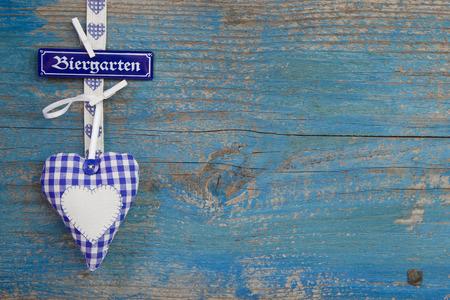 octoberfest: Blanco azul b�varo comprueba coraz�n en madera con signo beergarden en alem�n letras Foto de archivo