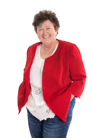 Attractive isolated smiling female pensioner wearing red jacket and jeans.