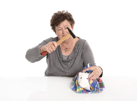 poorness: Isolated senior woman - money concept with a pensioner. Smashing piggy bank - poorness in the age. Stock Photo