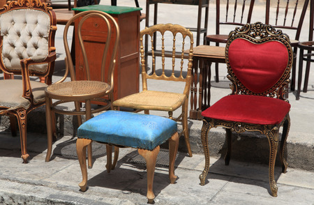 Collection of old antique and broken chairs on the flea market