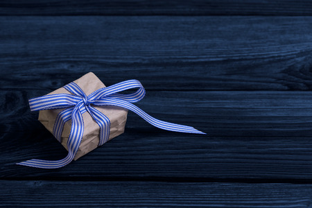 Isolated present with blue strips on wooden  photo