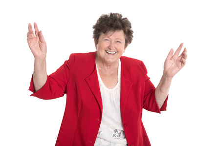 humorously: Isolated portrait of a happy and cheering older lady in red jacket