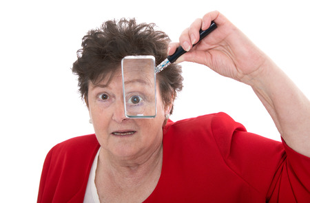 older woman: Portrait  Older isolated woman holding magnifying glass and is shocked