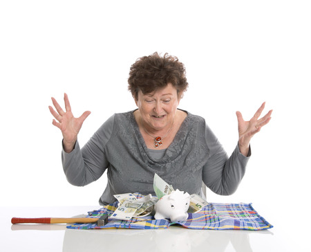 outgoings: Happy female pensioner after smashing her piggy box. Money concept for senior people. Stock Photo