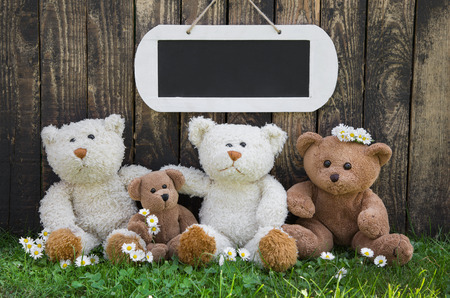 Happy teddy bear family in summer - concept wooden for a greeting card. photo