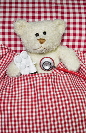 suffered: Sick teddy bear lying in a red checked bed. Concept for illness of children.