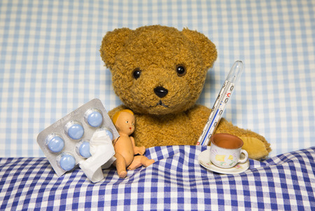 Sad and ill teddybear lying in bed - concpet for sick children. photo