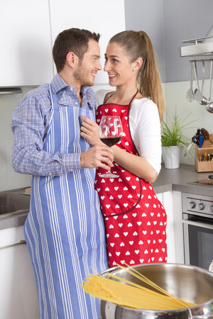 Young fresh married couple in the kitchen cooking together pasta and drinking red wine. photo