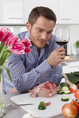 closing time: Single man in his kitchen after work drinking a glass of red wine.