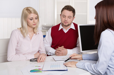 financial adviser: Financial business meeting: young married couple - adviser and clients sitting at desk.