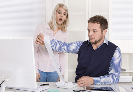 outgoings: Shocked and surprised businessman with his assistant sitting at desk controlling expenses and outgoings.