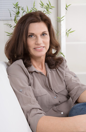 menopause: Attractive middle aged woman in portrait sitting on a chair. Stock Photo