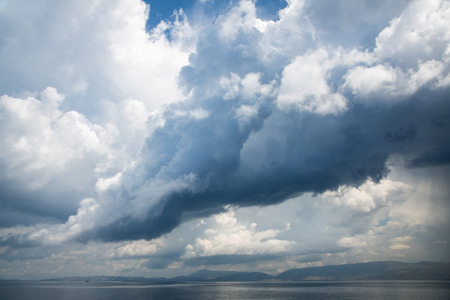 squall: Stormy weather like an hurricane with big rain clouds on the sea.