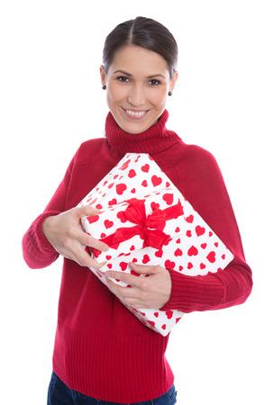 Isolated smiling young woman in red holding a present for christmas in her hands. photo