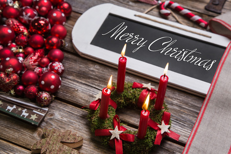 Merry christmas greeting card with four red candles and text in country style. photo