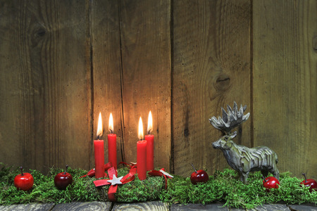 moos: Classic: Four red burning christmas candles on wood background with deer. Stock Photo