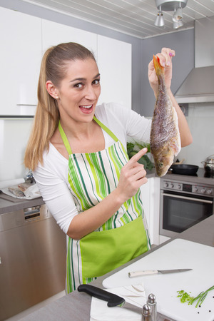 humorously: Woman in the kitchen preparing fish dinner with perch.