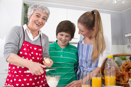 Fat kid: Three generations living together - happy family cooking together with the grandmother. Stock Photo