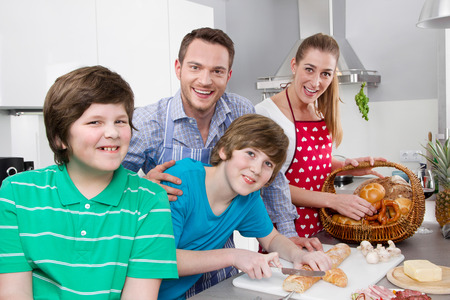 Happy young family in the kitchen preparing breakfast on sunday. photo