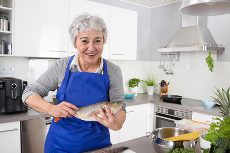 households: Older grey-haired woman in the kitchen preparing fresh fish.
