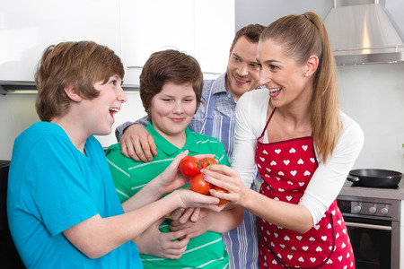 Happy young family have fun in the kitchen - cooking together on weekend. photo