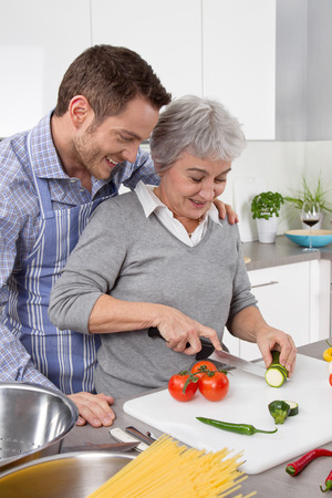meat lover: Young man and older woman cooking together in the kitchen and have fun. Stock Photo