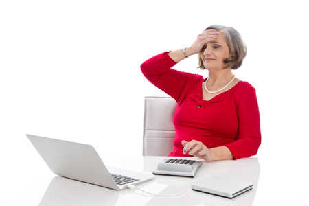 outgoings: Isolated portrait of a desperate senior female business woman sitting shocked at desk.