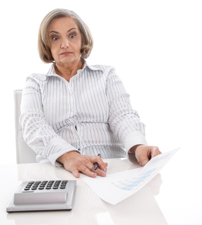 Surprised senior businesswoman looking shocked at increasing costs. Stock Photo