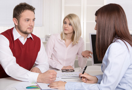 a marriage meeting: Financial business meeting: young married couple - adviser and clients sitting at desk.