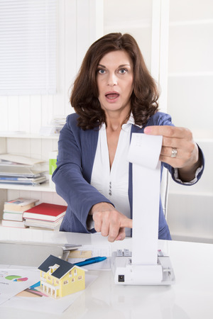 financial controller: Shocked and frustrated business woman controlling expenses of the company.