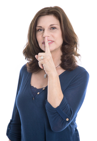 discretion: Concept for discretion: isolated mature woman touching finger on mouth.