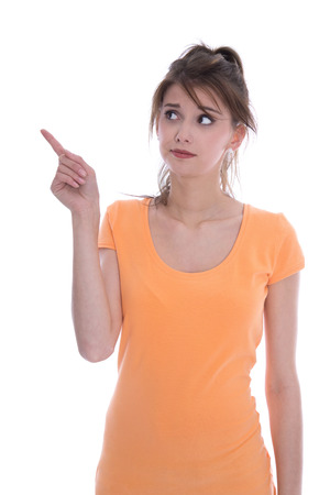 Portrait of an anxious isolated young girl in orange pointing with her finger over white. photo