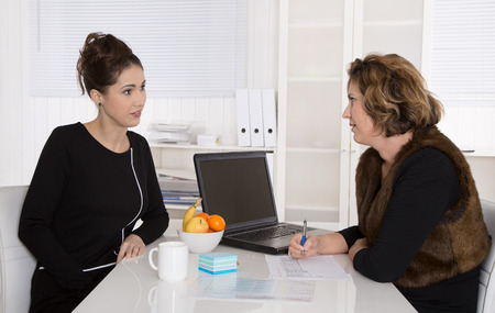 interviewing: Two businesswoman sitting at desk talking together in the office.