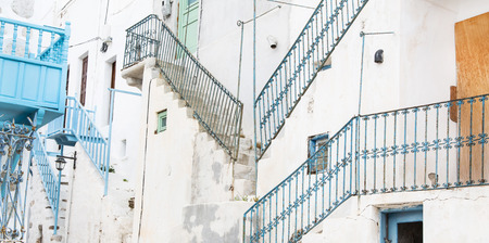 Architecture on the Cyclades. Greek Island buildings with her typical blue doors and white houses with old balcony railings. photo