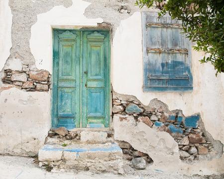 Staré dřevěné dveře ze zchátralého poškozený fasádě domu nebo zepředu v modré, zelené a tyrkysové