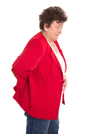 suffered: Isolated female senior in red has backache or rheumatism wearing jacket  Stock Photo