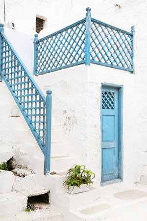 Architecture on the Cyclades. Greek Island buildings with her typical blue and White houses and flowers at the entrance. photo