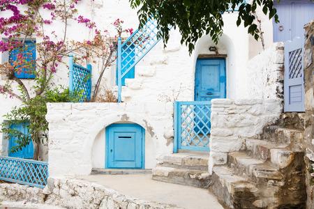 キクラデス諸島の建築。彼女の典型的な青い扉と白い家のギリシャの島の建物。